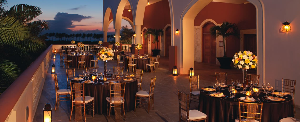 A nighttime set-up on the patio showcasing expansive views of the Caribbean Sea and manicured gardens.