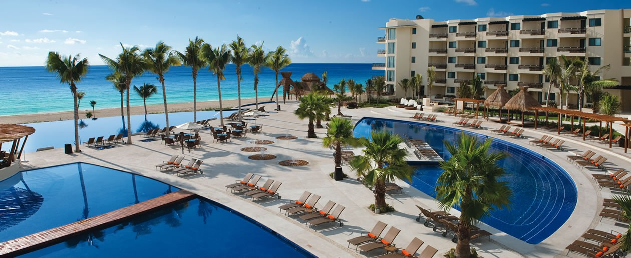 A Dreams Riviera Cancun Resort & Spa aerial of the pools with views of the turquoise sea.