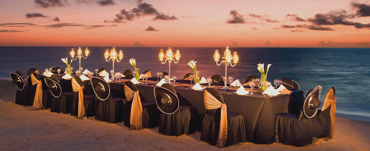 A dinner set-up on the beach during sunset offers stunning views of the Caribbean.