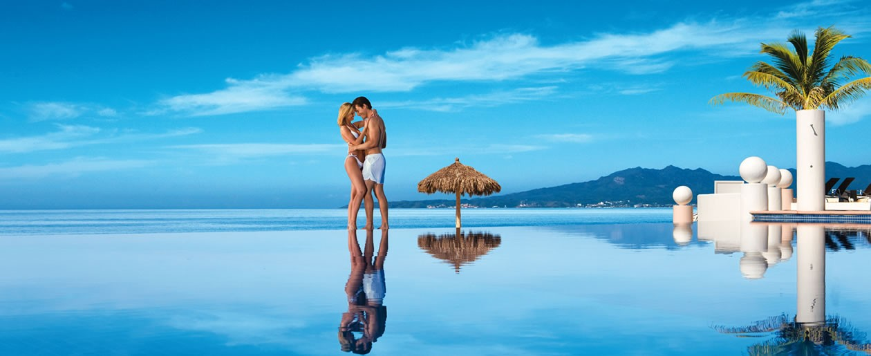 A couple is reflected against the sky in the beautiful infinity pool.