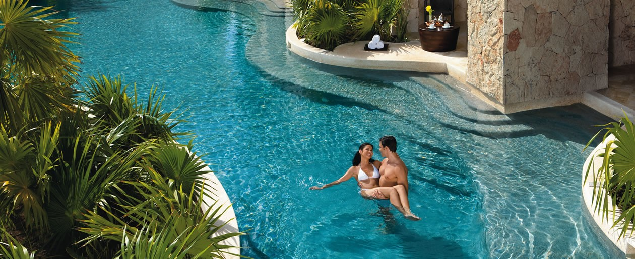 Couple relaxing outside of their swim-out suite which leads directly out to the meandering pool.