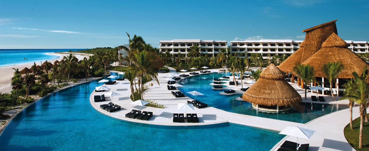 A property overview of Secrets Maroma Beach Riviera Cancun shows bars and restaurants located under thatched palapas, bordered by shimmering pools and the gorgeous white sand of Maroma Beach.